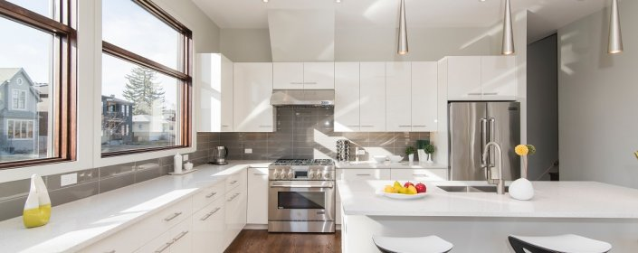 Beautiful, clean, white modern kitchen with lots of natural light from windows