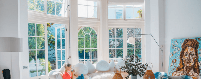 woman enjoys coffee in large living room with beautiful bay windows